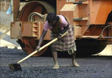 A woman works at a road construction site.