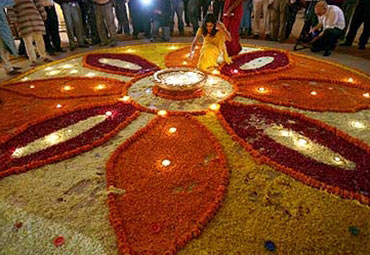 A woman lights up lamps during Diwali mahurat trading at Bombay Stock Exchange.