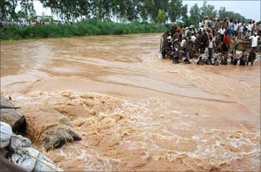 Soldiers repair SYL canal after it was damaged by heavy rains as villagers watch in Kurukshetra.