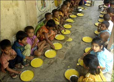 Students have a free meal distributed by a government-run school in Nalchar village, near
