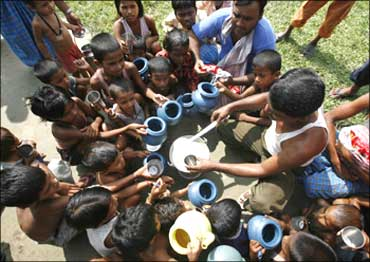 Flood-affected children crowd around a relief worker distributing free milk at a flood relief camp in Purniya in Bihar.
