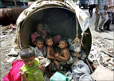 Children eat in their make-shift home in an unused waterpipe in Mumbai.