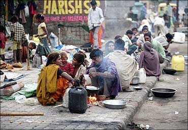 Homeless people prepare their food on roadside in Ahmedabad.