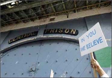 An employee of Satyam Computer Services holds aloft a placard outside the gate of Chanchalguda jail.