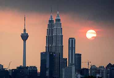The sun sets near the Petronas Twin Towers.