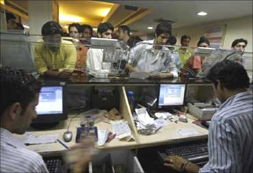 Customers queue up at a bank counter.