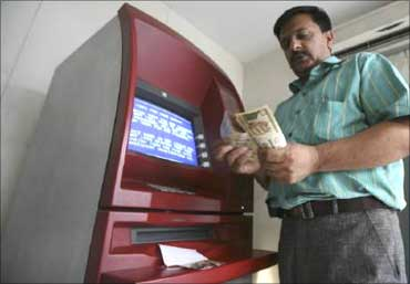 A man withdraws cash frm an ATM.