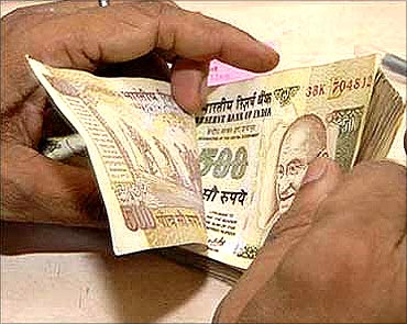 A bank employee counting rupee notes.