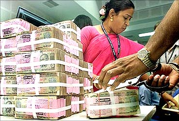 RBI employees with stacks of bank notes.