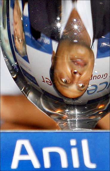 Anil Ambani is reflected in a glass while speaking to journalists.