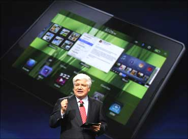 Mike Lazaridis, president and co-chief executive officer of IM, holds the new Blackberry PlayBook with a screen projection of the devic.