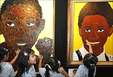 Students gather next to paintings of US President Barack Obama.