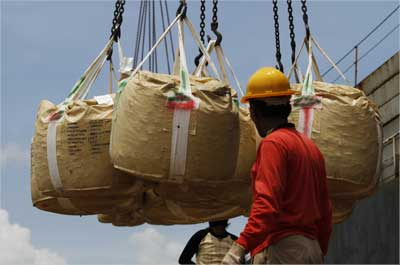 Workers load bags of nickel ore.