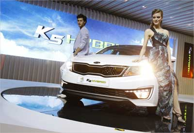 Models pose with Kia Motors' K5 Hybrid during a media preview of the Seoul Motor Show in Goyang.