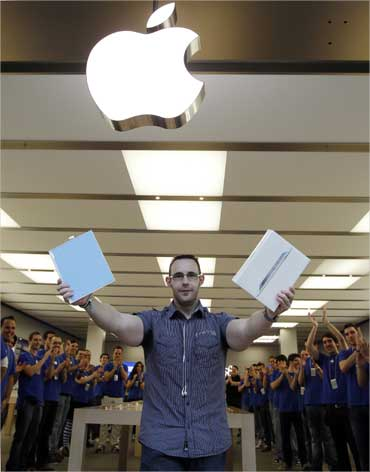 The first Madrid customer to buy an iPad 2 tablet is applauded by Apple staff at a store.