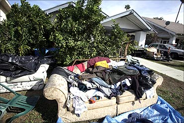 A pile of clothes and a sofa sit outside a foreclosed home in Los Angeles.