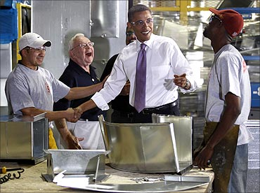 US President Barack Obama shares a laugh with workers during a tour of Stromberg Metal Works.