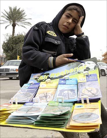 A boy sells air fresheners on a street in Baghdad.