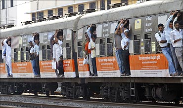 Commuters stand at the open doorways of a suburban train during the morning rush hour in Mumbai.