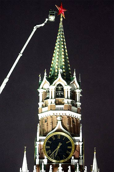 Workers remove snow from a star on the Spassky Tower of the Kremlin in central Moscow.