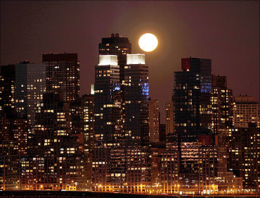 A full moon rises over the skyline of Manhattan along the Hudson River in New York.