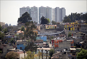 New buildings are seen behind a low-income neighborhood in Mexico City.
