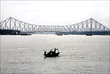 Fishermen row a boat on the Hooghly River against the backdrop of Howrah bridge in Kolkata.