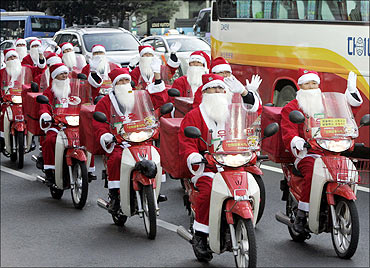 Postmen dress as Santa Claus ride on their delivery motorbikes in Seoul.