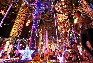 Families watch the symphony of lights attraction at park in Manila's Makati financial district.
