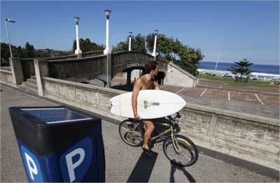 A surfer rides his bicycle next to a solar-powered parking meter at Bondi beach in Sydney.