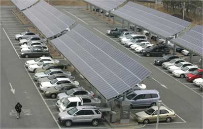 A man walks beside solar panels at a parking lot in Kwangju, Seoul.