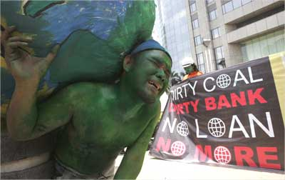 An environmental activist carries a globe during a protest near the World bank office in Jakarta.