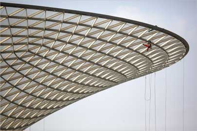 A worker cleans the exterior of the Sunny Valley, a structure to harness solar energy, at Shanghai.