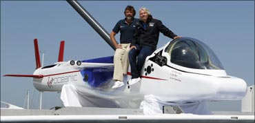 Richard Branson and Chris Welch pose on top of a solo piloted submarine during a photo opportunity at a news conference in Newport Beach, California on April 5, 2011.