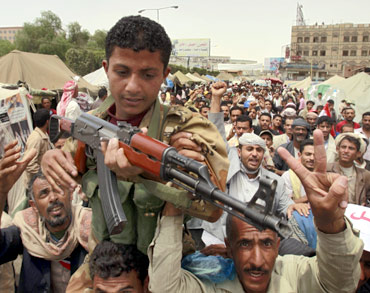 Protesters carry an army soldier after he took part in clashes with supporters of Yemeni President.