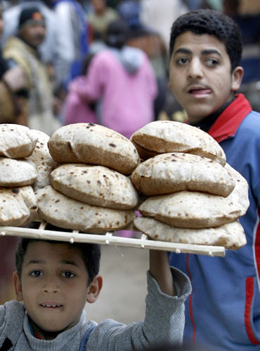 A child carries a tray of bread on his head in Cairo.