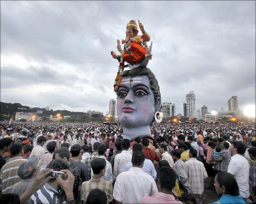Devotees watch idols of the Hindu elephant god Ganesh, the deity of prosperity and Lord Shiva during