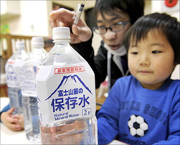A child holds a bottle of emergency long shelf-life mineral water at a nursery school in Tokyo.