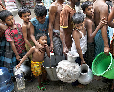 Children wait in a queue to collect water distributed by the army at the Jatrabari area in Dhaka.