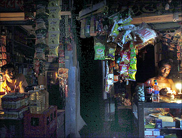 Vendors work in roadside shops during a power cut in an old part of Dhaka.