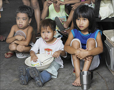 Children hold their bowls as they wait for free meals during a feeding program, Tondo, Manila.