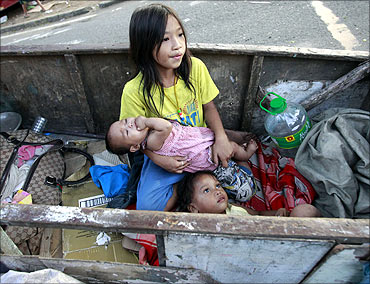 Children rest in a wooden cart after their shanty was burnt in a fire at a slum in Quezon, Manila.