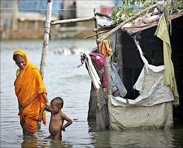 A woman wades through stagnant water with her child in the outskirts of Dhaka.