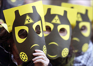 Anti-nuclear demonstrators holding placards protest at Sant Jaume square in central Barcelona.
