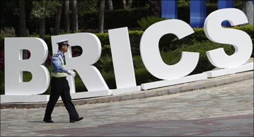 A policeman walks past a signage decoration for BRICS Summit outside Sheraton Hotel, venue of BRICS Summit in Sanya, China.