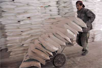 A worker unloads bags of flour at a foodstuff wholesale market in Shenyang, China.