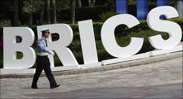 A traffic policeman walks past a signage decoration for BRICS Summit outside the Sheraton Hotel, Sanya.