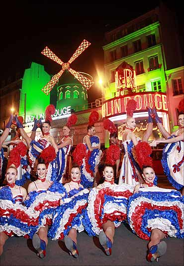 Dancers from the Moulin Rouge in Paris perform their traditional Cancan outside the cabaret.