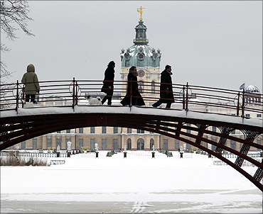 People walk over a bridge in front of snow covered Charlottenburg castle in Berlin.