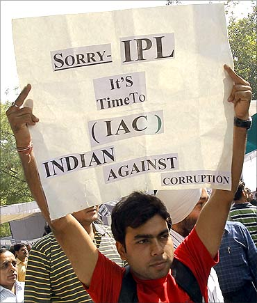 Supporters of Anna Hazare hold placards as they protest against corruption.